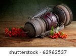 Still Life Autumn concept image with berries and old lamp - stock photo