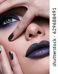 Small photo of Young beautiful showy girl portrait covers her face with her hand. Close-up, green eyes, pouting lips, long fingers. Matte gray lipstick metallic, nail polish. Blue shadows. Cosmetics.