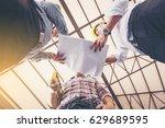 contractor and engineer discuss ... | Shutterstock . vector #629689595