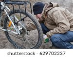 a man lubricates a bicycle with ... | Shutterstock . vector #629702237