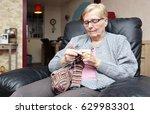 an elderly woman is knitting... | Shutterstock . vector #629983301