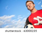 Football or soccer goalkeeper holding the ball outdoors - stock photo