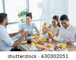 Stock photo business colleagues interacting with each other while having breakfast in office cafeteria 630302051
