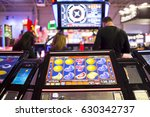 A slot machine monitor is seen in a casino with silhouettes of people in the background. Fruits at the monitor of the slot machine.