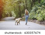 Stock photo girl walking in the park with his dog girl playing with a dog at the beach and in the park 630357674