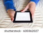 Small photo of Woman reading on her electronic book (e-book) on the bed at home. Hands only. Red nail polished fingers. Blue sleeves.