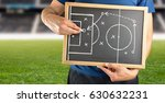 Small photo of hand of a football coach drawing a tactics of soccer game with white chalk on blackboard at stadium background