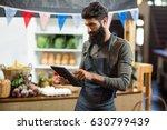 Vendor Using Digital Tablet At...