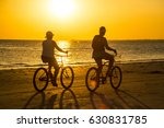 Stock photo couple rides bicycles in sunset rays on sanibel island 630831785