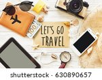 Small photo of travel. let's go travel text sign concept on card flat lay, camera sunglasses compass passport money phone hat shells on white wooden background top view. wanderlust and adventure