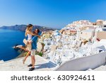 Young couple looks down on the landscape of the island of Santorini