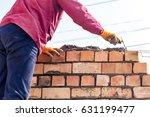 worker builds a brick wall in... | Shutterstock . vector #631199477