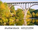 A locomotive passes under a high arch bridge in a scenic area - stock photo