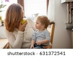 mother and son eating an apple... | Shutterstock . vector #631372541