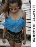 Small photo of curly latina on beach , girl on wooden bridge