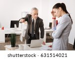 Small photo of Angry boss standing opposite his secretary