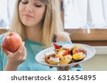 diet. woman holding sweets ... | Shutterstock . vector #631654895