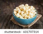 popcorn in a blue bowl on a... | Shutterstock . vector #631707314