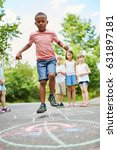 Small photo of African boy playing hopscotch and jumping with ambition and concentration