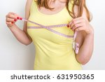 slim woman measures her breast... | Shutterstock . vector #631950365