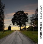 Country road with silhouette of tree against colorful sky - stock photo
