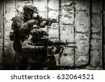 Pair of Army Rangers with rifle and machine gun moving along the concrete wall on mission. They are ready to start firing if enemy appear. Outdoor location shot - stock photo