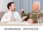Small photo of Elderly man and manager signed contract car hire at home and hand over keys
