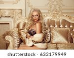 Small photo of Beautiful alluring blond woman in fur coat sitting on royal sofa in luxury modern interior. Beauty glamour fashion style photo portrait.