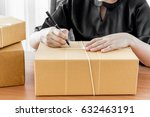 woman signs papers among parcels | Shutterstock . vector #632463191