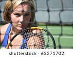 Female tennis player with determined stare through the net - stock photo
