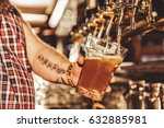 male arm filling cup of beer | Shutterstock . vector #632885981