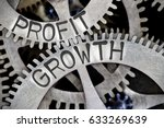Small photo of Macro photo of tooth wheel mechanism with PROFIT GROWTH letters imprinted on metal surface