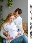 Small photo of Cropped image of beautiful pregnant woman and her handsome husband. Husband touching his wife belly with hands
