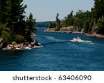 Motor boat passing through a narrow channel - stock photo