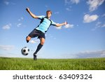 Handsome male football player kicking the ball - stock photo