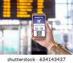 Small photo of Boarding pass in mobile phone. Woman holding smartphone in airport with modern ticket on screen. Easy and fast access to aeroplane. Terminal and timetable in the blurred background.