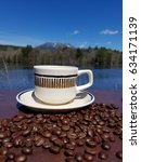 Small photo of A mug and saucer on a small table surrounded by roasted coffee beans with the Penobscot river and Mt Katahdin in the background.
