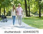 Small photo of Senior man walking in the park with walking frame accompanied by his caregiver