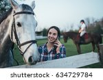 Stock photo beautiful young woman enjoying with her horse and talking on phone at ranch 634729784