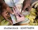 market vendor counts money in... | Shutterstock . vector #634976894