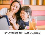asian mother and daughter using ... | Shutterstock . vector #635022089