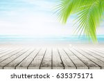 empty wooden table and palm... | Shutterstock . vector #635375171
