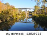 A high arched bridge reflected in a deep blue river in autumn - stock photo