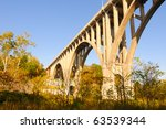 A high arched bridge in morning sunlight spanning a wide valley - stock photo