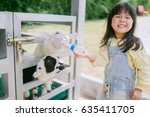 sheep feeding.little asian girl ... | Shutterstock . vector #635411705