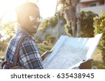 Small photo of Outdoor shot of happy adventurous young dark-skinned traveler studying paper map in his hands while having road trip in foreign country, looking for new amazing places, people and adventures