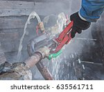 A Plumber Fixes A Water Leak O...