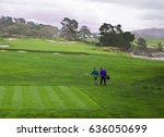 Small photo of Golfer and caddie walk away from tee and onto beautiful green fairway, enjoying a round of golf on a cool and cloudy day