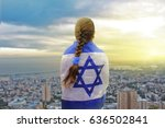 Small photo of Lonely patriot jewish girl standing and looking at the sunrise in Haifa with the flag of Israel wrapped around her. Newcomer life and immigration to Israel concept.
