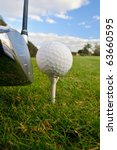 golf ball on tee with driver club ready with morning dewy grass - stock photo